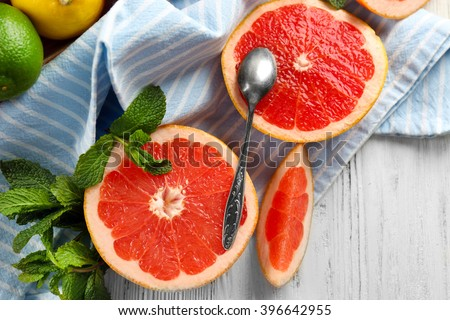 Pieces of grapefruit with spoon on wooden light background - stock photo
