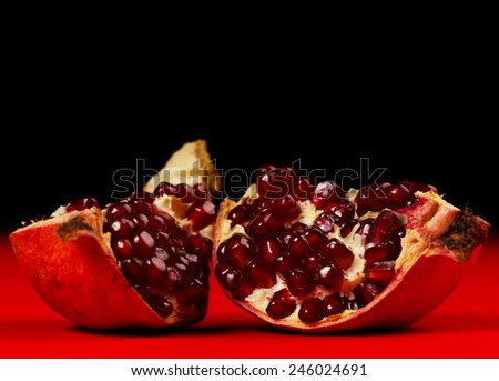 Pieces of grenadine over red and dark background - stock photo