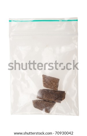 pieces of hashish in a plastic bag , photo taken with a macro lens,  isolated on a white background - stock photo