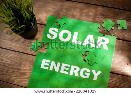 Pieces of jigsaw puzzle on a wooden board with a word SOLAR ENERGY written on them. - stock photo