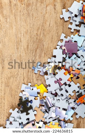 Pieces of jigsaw puzzle on wooden background - stock photo