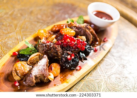 pieces of lamb cooked on the grill. served with fruit - stock photo