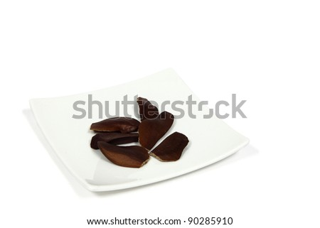 Pieces of mahogany fruit/skyfruit (Swietenia Macrophylla) which is an alternative herb medicine for diabetes (eaten raw) on white plate  on white background