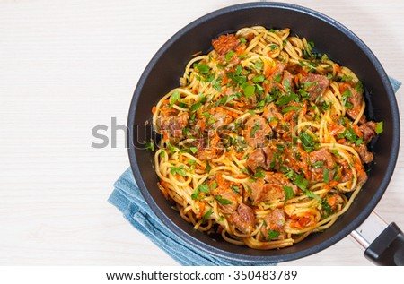 pieces of meat and vegetables with spaghetti in a frying pan - stock photo