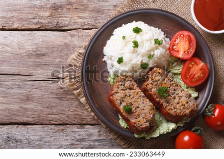 pieces of meat loaf and rice, vegetables on a plate close-up, horizontal view from above  - stock photo
