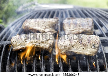 pieces of meat on the barbecue, flames present around them - stock photo