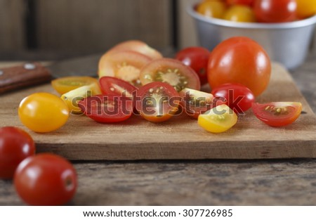 pieces of organic colorful tomatoes were cut on chopping block, pieces of colorful tomato with rural atmosphere. colorful tomato on old wood background. fresh tomatoes. - stock photo