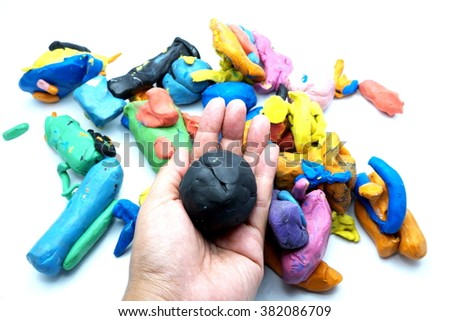 Pieces of plasticine with hand, isolated on white background. Focus on pieces on hand. Space for texts. - stock photo