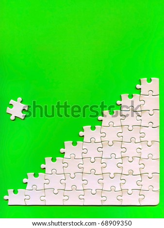pieces of puzzle on a green background - stock photo