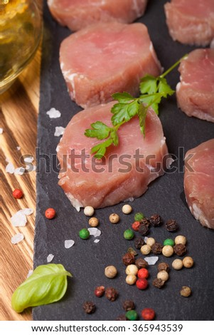 Pieces of raw meat on a plate of slate herbs spices and olive oil on a new burned wooden background. Selective focus. - stock photo