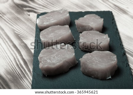 Pieces of raw meat on a plate of slate on a new burned wooden background. Selective focus. Toned. - stock photo