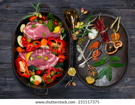 Pieces of raw meat, vegetables and various kind of spices in a pan, top view - stock photo
