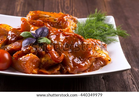 Pieces of raw pork on white plate. Chunks of barbecue in a sauce. Pieces of raw pork in barbecue sauce on a white plate with tomato basil dill. - stock photo