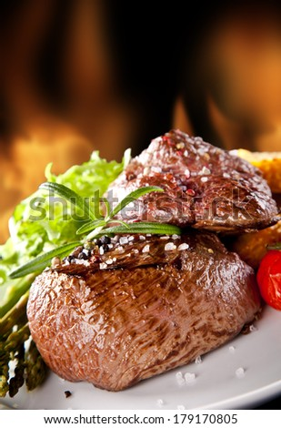 Pieces of red meat steaks with rosemary served on black stone surface. Blur fire flames on background - stock photo