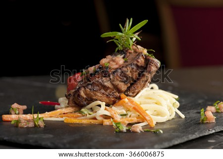 Pieces of red meat, steaks with vegetable and spices, served on black stone surface. selective focus - stock photo