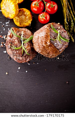 Pieces of red meat steaks with vegetable and spices, served on black stone surface. Shot from upper view - stock photo