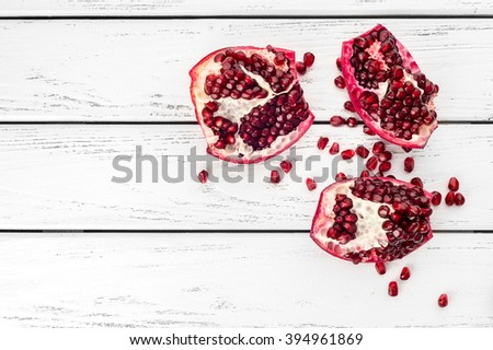Pieces of ripe juicy pomegranate and pomegranate seeds on a white wooden plank background.