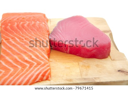 pieces of salmon , red tuna, and sole fish on wooden plate isolated on white background