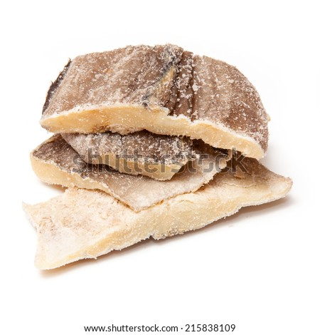 Pieces of salt cod fish isolated on a white studio background. - stock photo