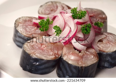Pieces of salted mackerel and red onion on white background - stock photo