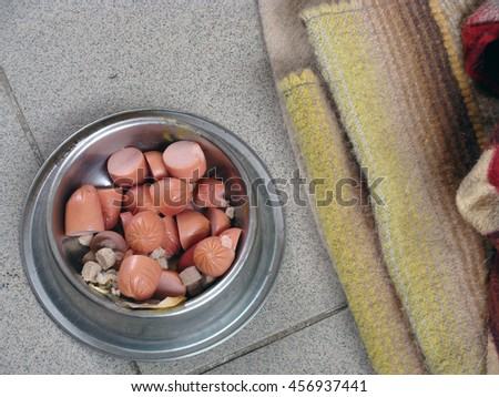 Pieces of sausage in metal dish for dog or cat on tiled floor close up.