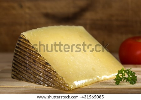 Pieces of sheep milk cheese on wooden background - stock photo