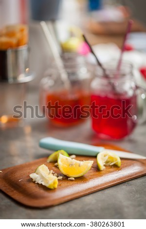 Pieces of sliced lemon on wood board on concrete bar in cafe with low key scene