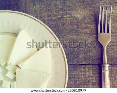 Pieces of soft white cheese on plate and vintage fork over wooden background. on raw wooden background. Grunge style. - stock photo