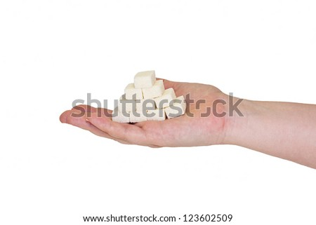 Pieces of sugar on a female hand isolated