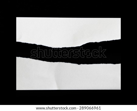 Pieces of torn white paper on black background. - stock photo