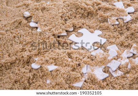 Pieces of white jigsaw puzzle buried in sand - stock photo