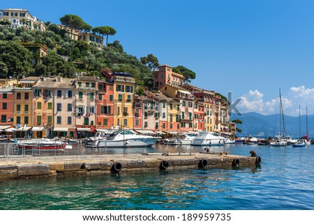 Pier and boats on bockground of colorful houses in bay of Portofino, Italy. - stock photo