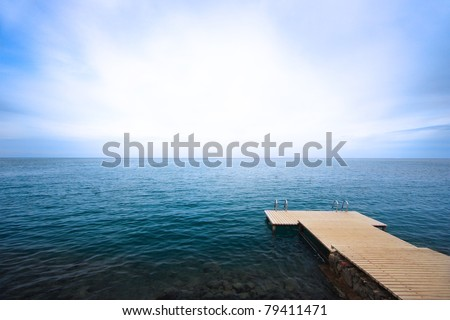Pier and the sea at sunrise - stock photo