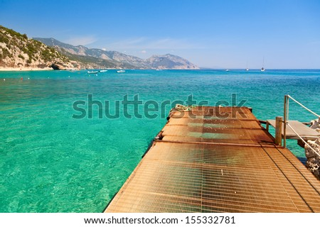 Pier at cove with clear turquoise water in Sardinia - stock photo