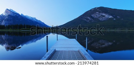 Pier at Dawn over still waters - stock photo