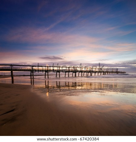 pier at dawn with interesting reflections and smooth clouds formation at square format - stock photo