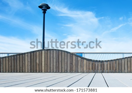 Pier at the seaside with street lamp and beautiful blue sky and clouds - stock photo