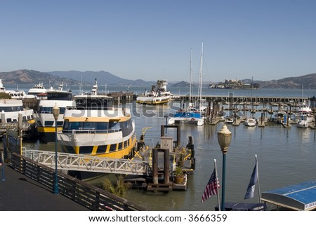 Pier 39 boats and Alcatraz in the background in San Francisco California - stock photo