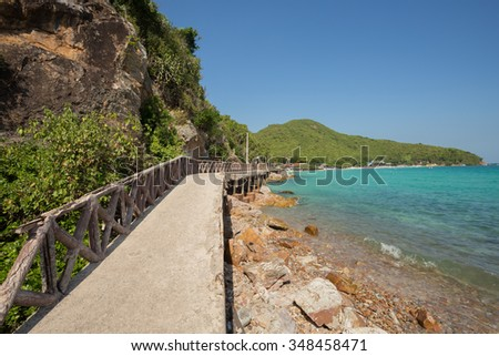 Pier extending out over the blue green sea with serenity beach - stock photo