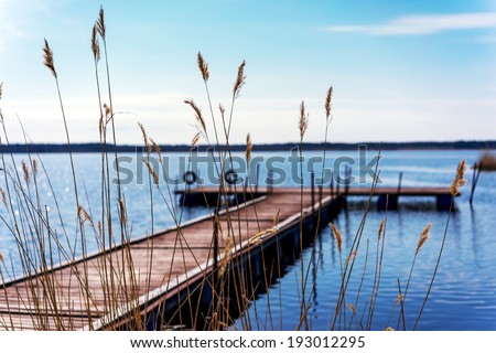 Pier for pleasure and fishing boats on shore of Lake Ladoga in Karelia. Soft focus. In the foreground the tall grass - stock photo