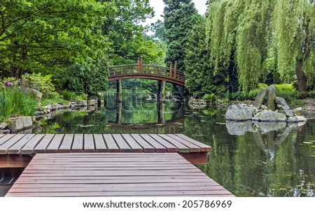pier in japanese garden with red japanese bridge in background - Red Japanese Garden Bridge