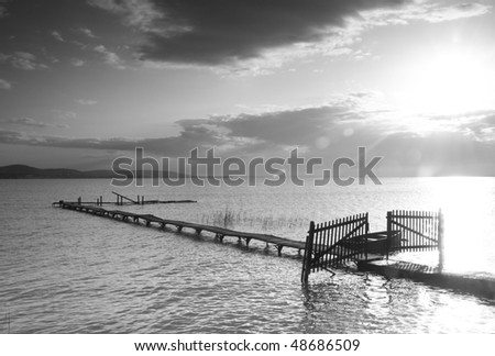 Pier in light glittering with a boat and a gate