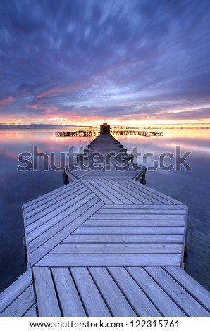 Pier in zigzag at twilight - stock photo