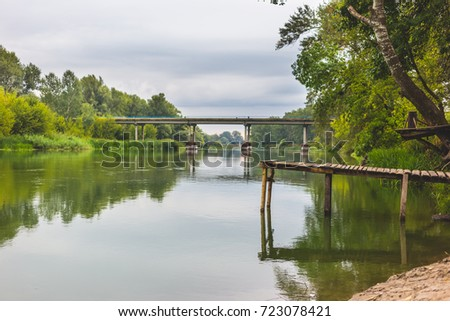 Pier on a calm river in the summer. Wooden pier bridge in the morning. Place for fishing in the river. Toned, style photo.