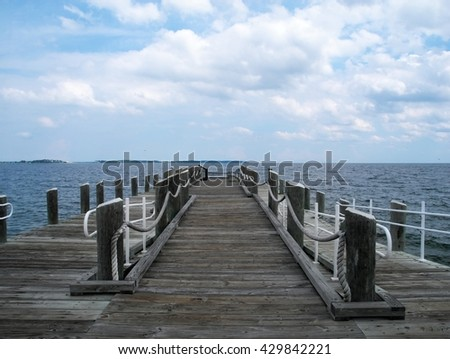 Pier on cloudy summer afternoon. Cold lake water. Grey wooden pier. Deserter, abandoned place. Relaxing and calm. Windy weather.  - stock photo