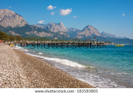 Pier on shingle beach and aquamarine water in popular touristic resort of Kemer on Mediterranean sea in Turkey. - stock photo