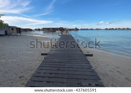 Pier on sunny day with white clouds and sun    - stock photo