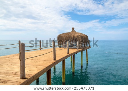 Pier on the seashore with a tropical hut - stock photo