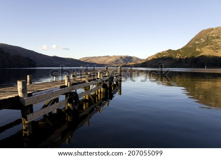 Pier on Ullswater in the Lake District, England, with mountain reflections