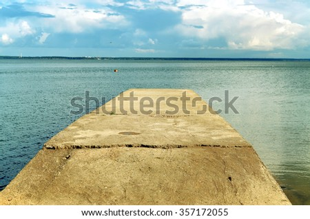 Pier stretching into the sea in the summer in good weather - stock photo